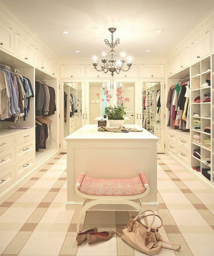 Elegant white ladies custom closet design with island and chair